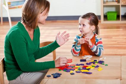 Little girl (3 years) listening to preschool teacher (30s) in classroom.